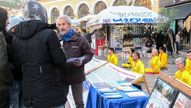 Passersby at Athens Railway Station listens to a practitioner explaining Falun Dafa