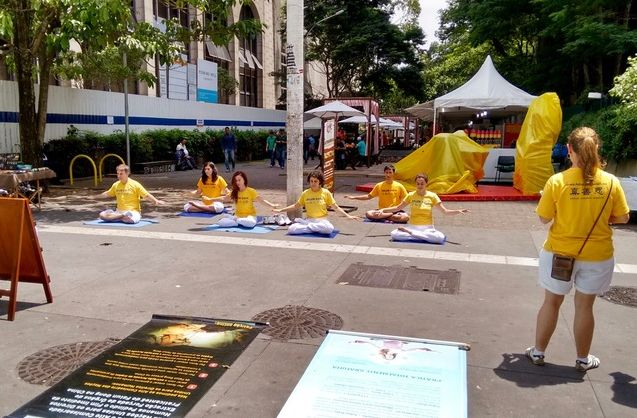 Practitioners demonstrate the meditation exercise in Sao Paulo and reach out to the public to increase awareness of the persecution of Falun Dafa in China
