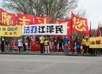 """Falun Gong practitioners hold banners in front of Xi's hotel. The white banners with blue and black texts read: """"Bring Jiang Zemin to Justice."""""""