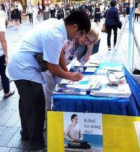 Christopti Mendoza signs a postcard to the Prime Minister.
