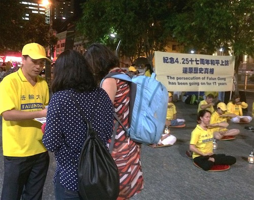 Passersby pause to learn about Falun Gong.