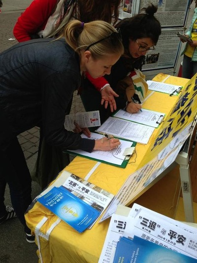 Two ladies sign the petition calling for the prosecution of Jiang Zemin.