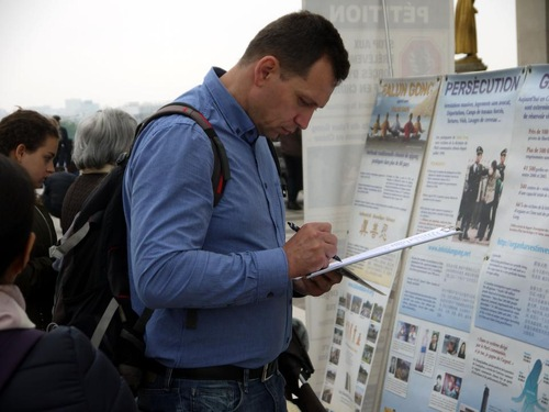 Tourists signing the petition to support Falun Gong.