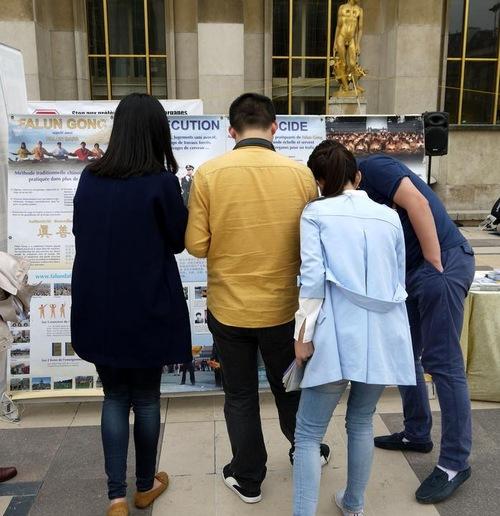 Chinese tourists reading about the persecution.