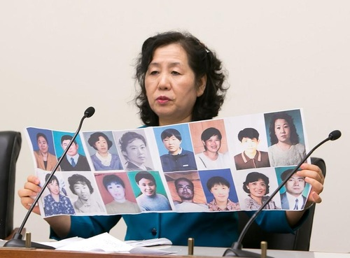 Ms. Wang Chunyan displays photos of her friends who were tortured to death because they refused to abandon their belief in Falun Gong.
