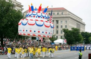 Falun Gong practitioners carry a large birthday cake balloon in the parade