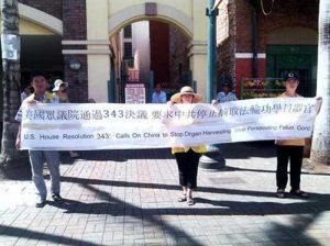 Falun Gong practitioners in Honolulu hold a large banner in Chinatown.