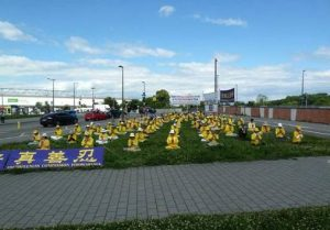 European Falun Gong practitioners holding group exercises on the grass near the parliament building.