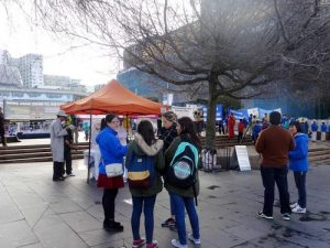 Passersby talking to Falun Gong practitioners