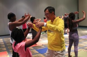 A practitioner teaches a young person the hand gestures of the Falun Gong exercises.