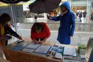 A passerby pauses to sign the petition, despite the rain.