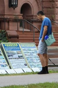 A passersby reads display boards introducing Falun Gong and raising awareness about the 17-year persecution of the practice in China.