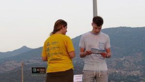 Falun Gong practitioner providing a brochure to a local of Lesvos.