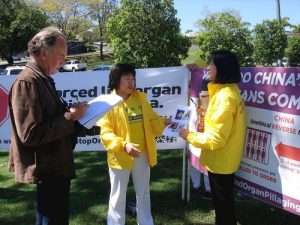 A reporter from the Gympie Times, a local newspaper, interviews Falun Gong practitioners.