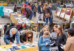 Many pedestrians signed petitions to support Falun Dafa practitioners.