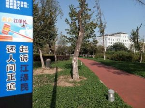 """The posters read, """"Bring Jiang Zemin to justice."""""""