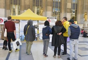 Passersby read posters to learn about Falun Gong and the persecution in China.