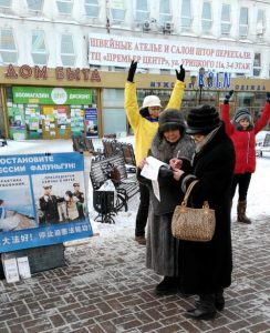 Two practitioners demonstrate the Falun Gong exercises while a passerby signs a petition in the City of Irkutsk, Siberia, Russia.
