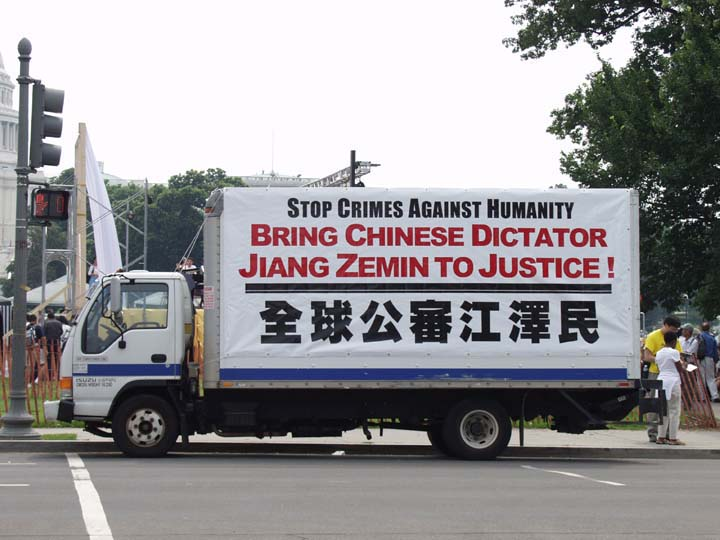 """A Truck Covered in Large Posters About """"Bringing Jiang to Justice"""" Slowly Travels the Streets of the Washington DC, USA."""