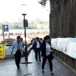 Chinese tourists see posters about Falun Gong near the Sydney Opera House in Sydney, Australia.