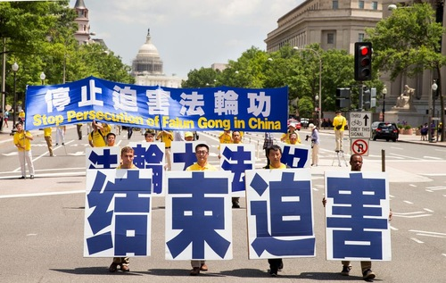 """More than 1,000 Falun Gong practitioners march in Washington D.C. on July 14, 2016, to protest the persecution of Falun Gong by the Chinese communist regime. The four practitioners in front are holding a banner which reads """"Stop the Persecution."""""""