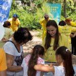 Lyudmila (long hair in yellow T-shirt) at a Falun Gong event.