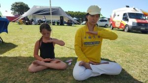 Seven-year-old Hineari does the sitting meditation with practitioners.