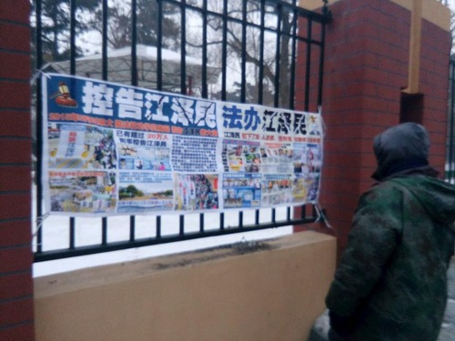 A passerby in Changchun City, Jilin Province, reads a poster about bringing former Chinese leader Jiang Zemin to justice for persecuting Falun Dafa.