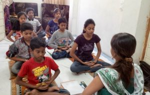 A practitioner leads the children in meditation.