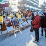 Passersby look at posters with Falun Gong information.