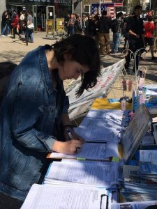 One young woman signs a petition.
