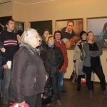 Visitors view the artworks and learn the stories behind the paintings.