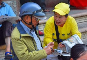 Distributing newspapers with Falun Gong information to passersby.