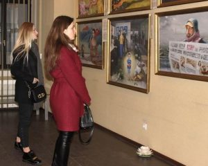 People visiting and viewing the artworks, learning the stories behind each painting.