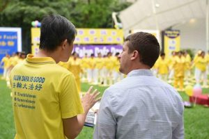 A passerby learns about Falun Gong at the World Falun Dafa Day celebration in Hong Lim Park on May 2, Singapore.