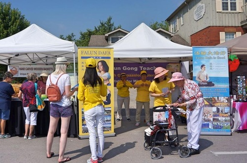 Falun Gong practitioners introduce the meditation during the Whitchurch-Stouffville Strawberry Festival on June 30, 2018.