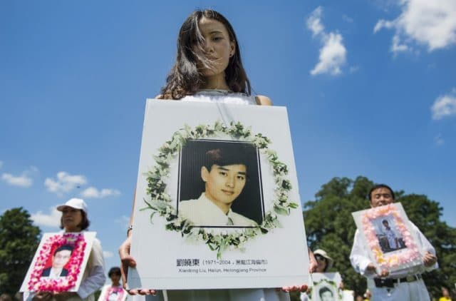 Falun Gong demonstrators hold memorial pictures as they march on Capitol Hill in Washington, DC