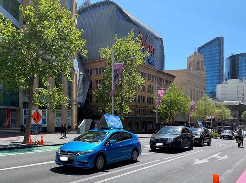The car parade passes through downtown Auckland.