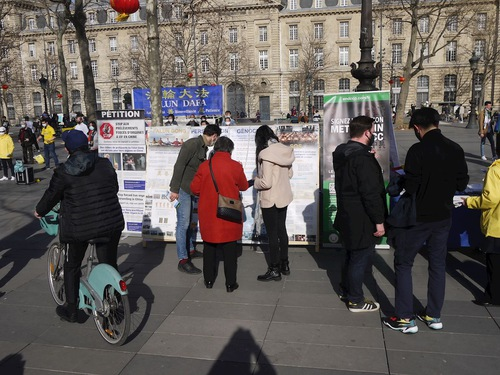 People stop by the practitioners' display on Place de la République and learn about Falun Dafa and the ongoing persecution in China.