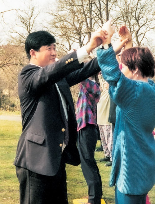 Master Li guides and corrects learners' hand movements while teaching Falun Dafa in Gothenburg in April 1995.