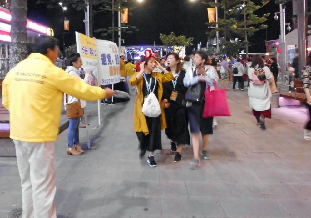 Falun Dafa practitioners offering a flyer to visitors.
