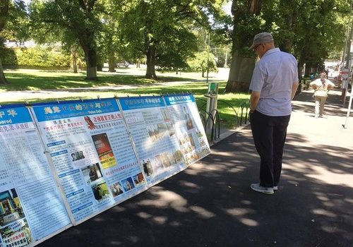 Passersby read informational posters about Falun Gong at Fitzroy Gardens in Melbourne.