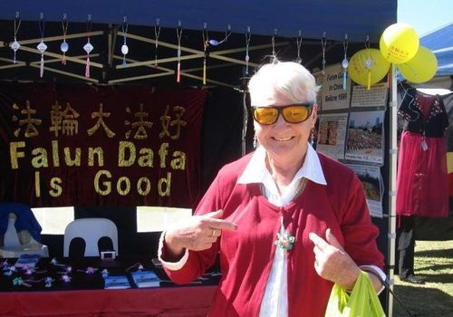 A festivalgoer wears the paper lotus flower she received at the Falun Gong booth.