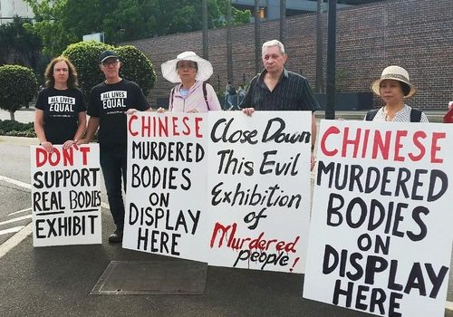 Mr. and Mrs. Grace (second and first from left) hold their own protest boards against the 'Real Bodies' exhibition.
