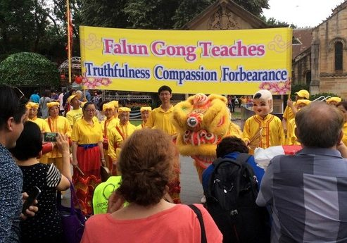 Falun Gong practitioners pose for photos at Centenary Square before the start of Chinese New Year celebrations.