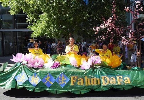 Practitioners demonstrate the Falun Dafa exercises on the float decorated with lotus and plum flowers.