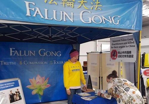 A visitor signs a petition to end the forced organ harvesting from Falun Dafa practitioners by the CCP in China.