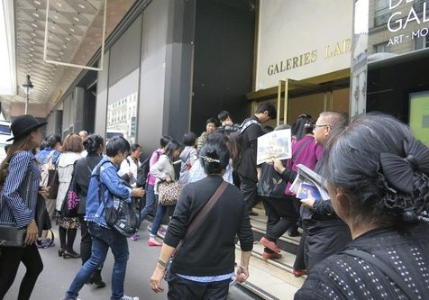 Chinese tourists read Falun Gong informational materials in front of Galeries Lafayette.